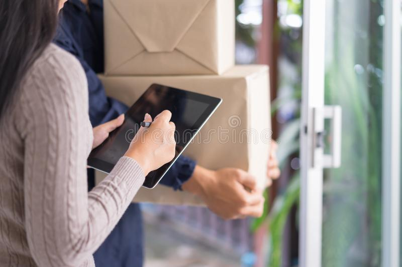 Fast and reliable service. Young woman signing on tablet pc comp. Uter at the entrance of her home. delivery man giving delivering parcel box stock photos