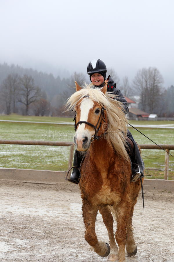 Fast riding girl. Smiling girl is riding on a fast horse royalty free stock photos