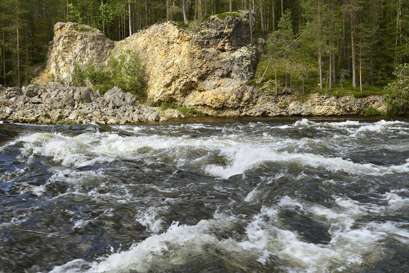 Fast river with stone banks. Finnish Lapland royalty free stock photos