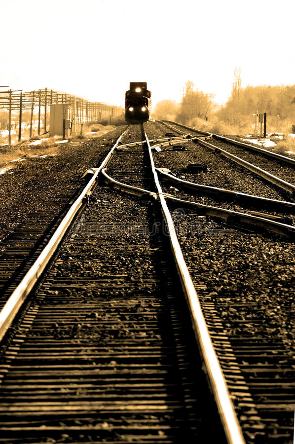 Fast Train on tracks. Distant train travelling fast on tracks with lights stock images
