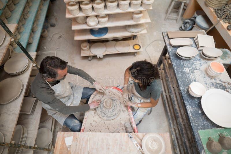 Fast utgift av den manliga keramikern som hjälper den kvinnliga keramikern royaltyfria foton