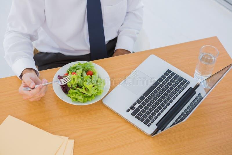Fast utgift av en affärsman som äter en sallad på hans skrivbord arkivbilder