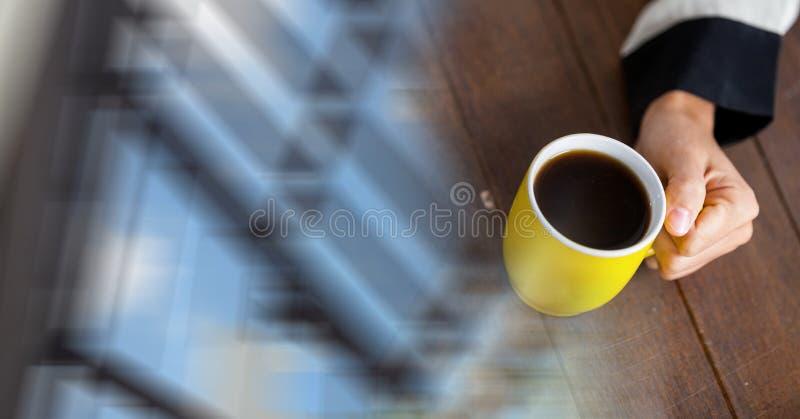 Fast utgift av handen med den gula kaffekoppen och oskarp fönsterövergång royaltyfria foton