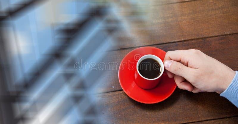 Fast utgift av handen med den röda kaffekoppen och oskarp fönsterövergång arkivfoto
