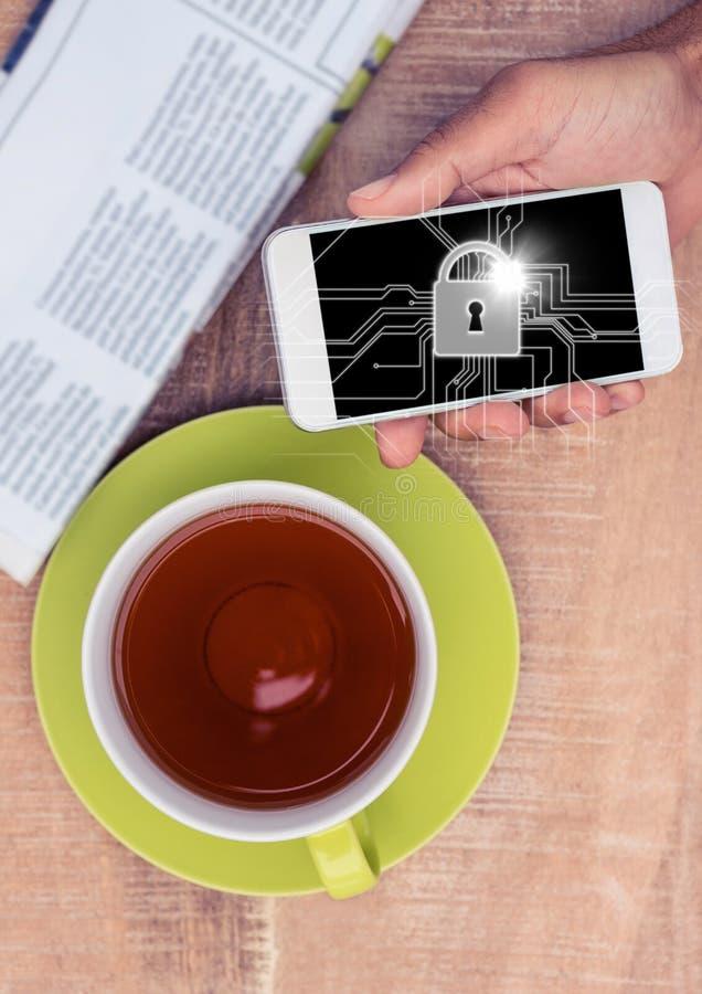 Fast utgift av handen med telefonen och te och vit låser diagrammet och blossar arkivbilder
