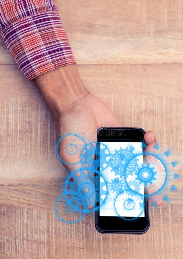 Fast utgift av handen med telefonvisningblått förser med kuggar diagram med signalljuset royaltyfri bild