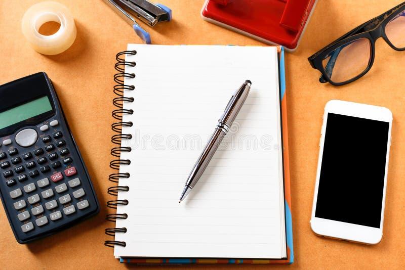 Fast utgift av kontorstabellen med anteckningsboken, penna, mobiltelefon, calc arkivbild
