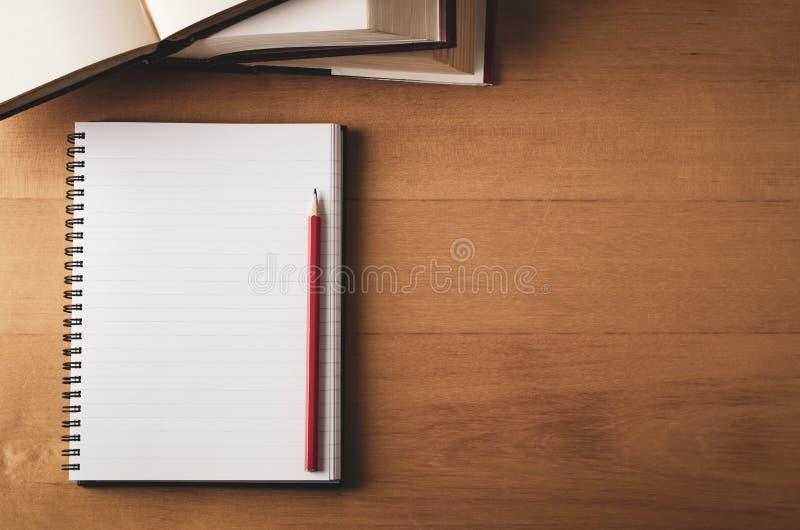 Fast utgift av skrivbordet med den öppnade anteckningsboken, läroböcker och blyertspennan royaltyfri fotografi