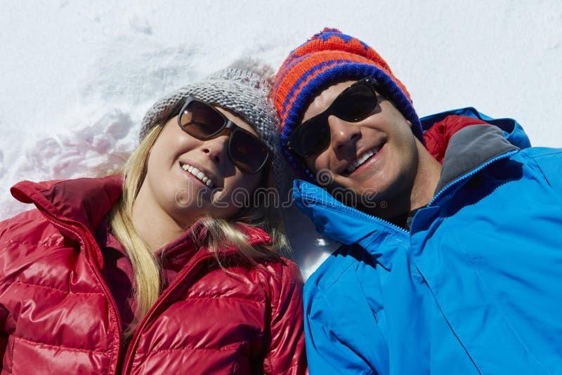 Fast utgiftskott av par som har gyckel på vinterferie fotografering för bildbyråer