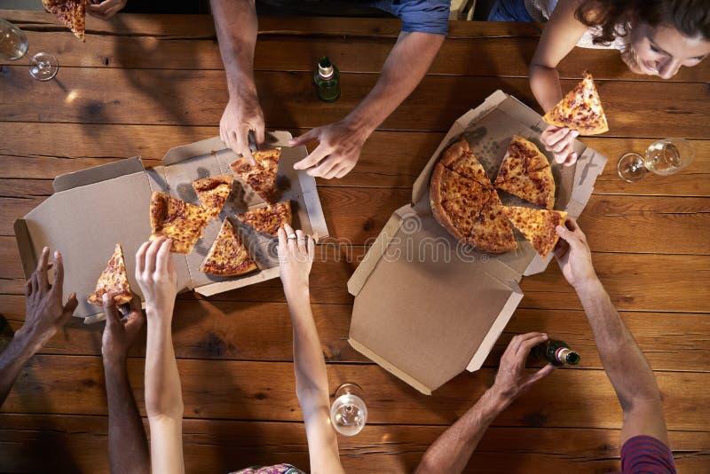 Fast utgiftskott av vänner på en tabell som delar tagande-bortpizza royaltyfri fotografi
