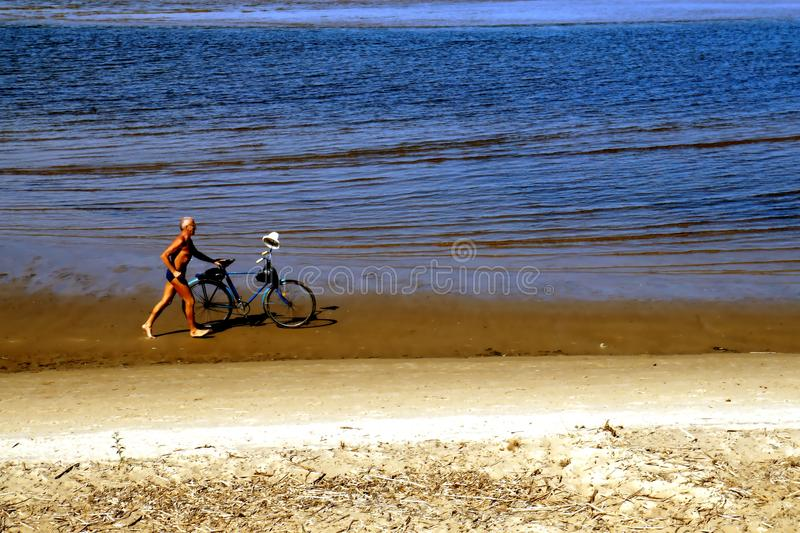 Fast walking on the beach. A man is brisk walking and pushing his bike on the beach in the morning stock photo