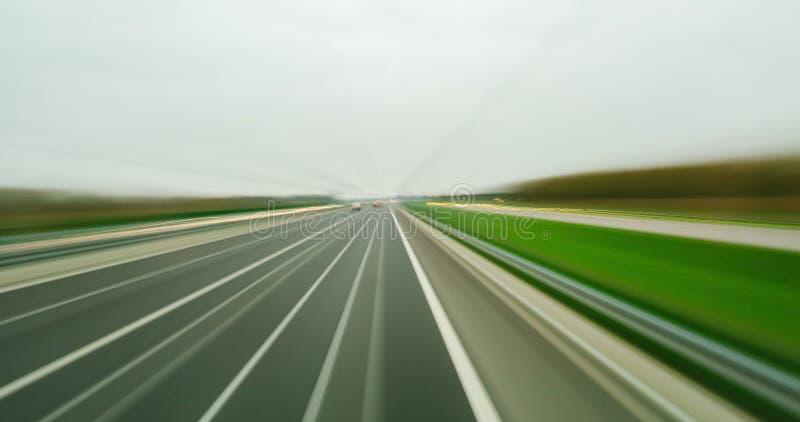 Fastar det suddiga fotoet för lång exponering av hög POV köra på en väg i staden med bilar, lastbilar royaltyfria bilder