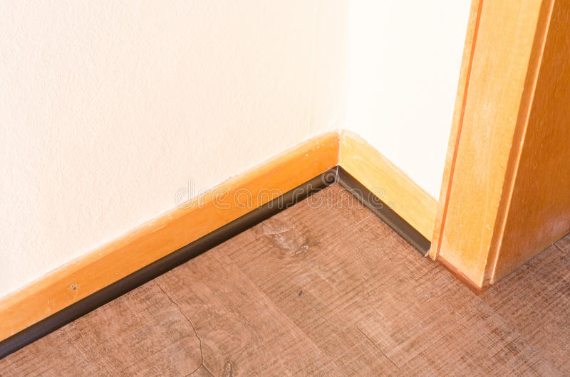 Fasten baseboard. Installation of a wood baseboard at the bottom of a wall after installing flooring stock photography