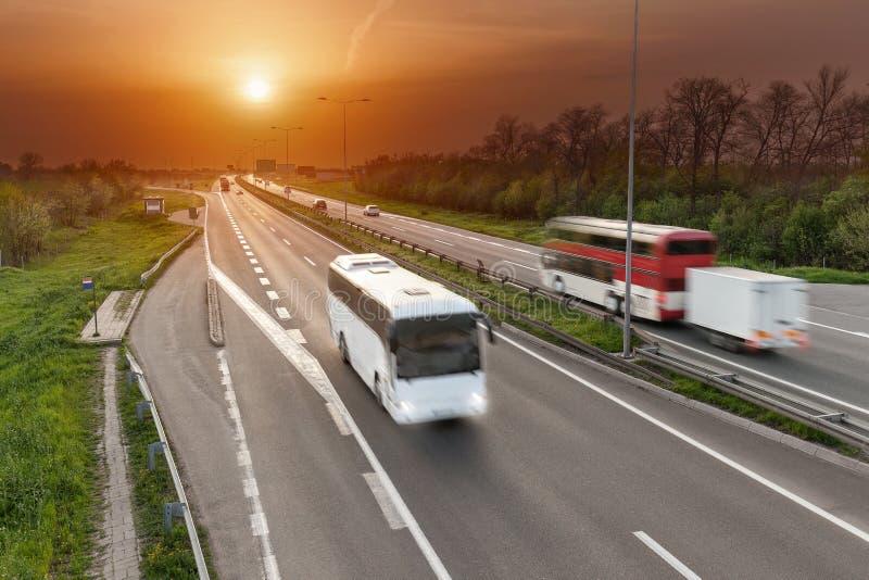 Fasten Reisebusse in der Bewegungsunschärfe auf der Autobahn bei Sonnenuntergang lizenzfreies stockbild