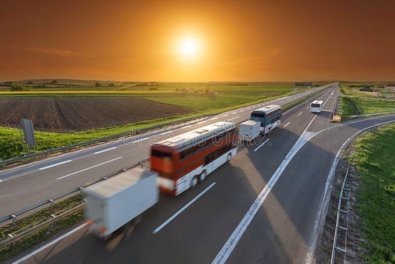 Fasten Reisebusse in der Bewegungsunschärfe auf der Autobahn bei Sonnenuntergang lizenzfreie stockbilder