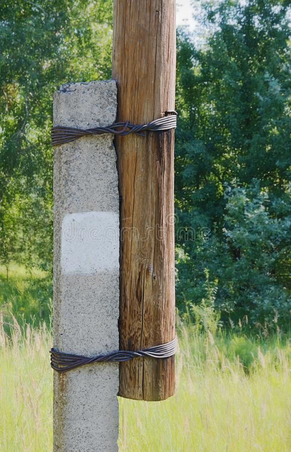 Fastening a wooden pillar to a support using wire. royalty free stock images