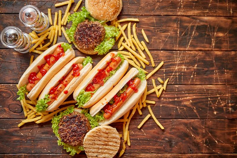 Fastfood assortment. Hamburgers and hot dogs placed on rusty wood table royalty free stock photography