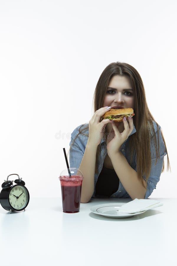 Fastfood en het Eten van Concept Jong Kaukasisch Wijfje met Hamburger en Kop van Rode Smoothie in Studio Het stellen in Gestreept stock fotografie