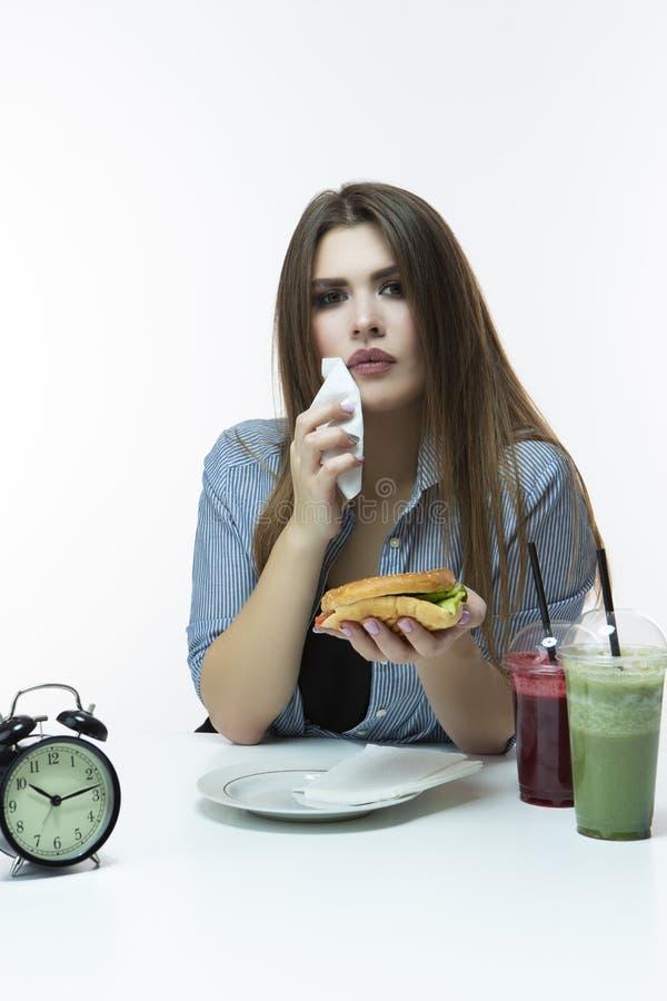 Fastfood en het Eten van Concept Jong Kaukasisch Wijfje met Hamburger en Kop van Rood en Groen Smoothie-Sap in Studio Binnen het  royalty-vrije stock afbeeldingen