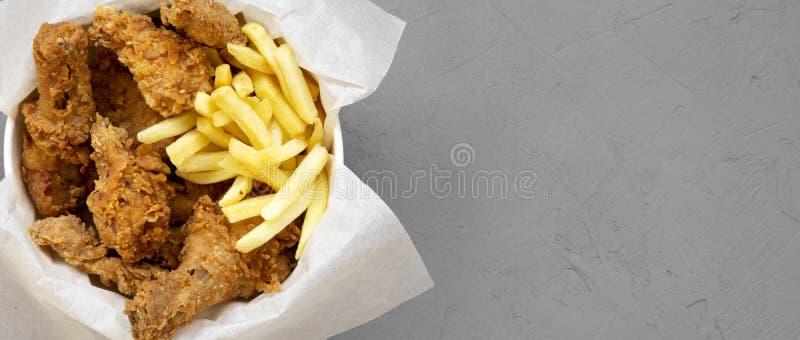 Fastfood: pieczonych kurczaków drumsticks, korzenni skrzydła, francuzów dłoniaki i kurczaków paski w papierowym pudełku nad szary zdjęcia stock
