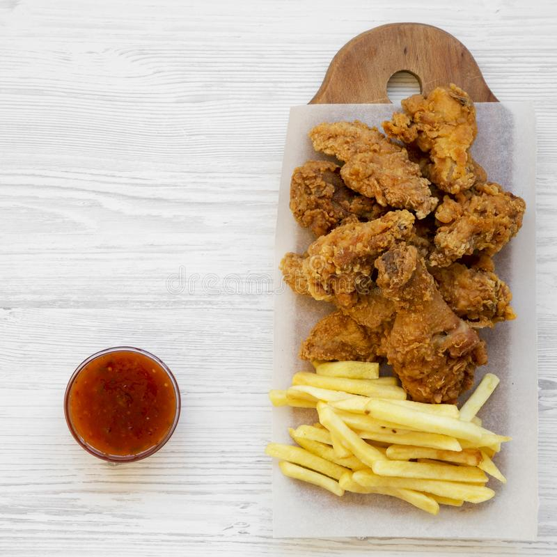 Fastfood: pieczonych kurczaków drumsticks, korzenni skrzydła, francuz smażą i kurczak dotyka z cukierki kumberlandem nad białą dr zdjęcie stock