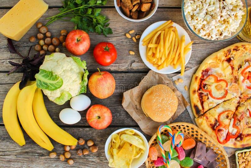 Fastfood und gesundes Lebensmittel auf altem hölzernem Hintergrund stockfotos
