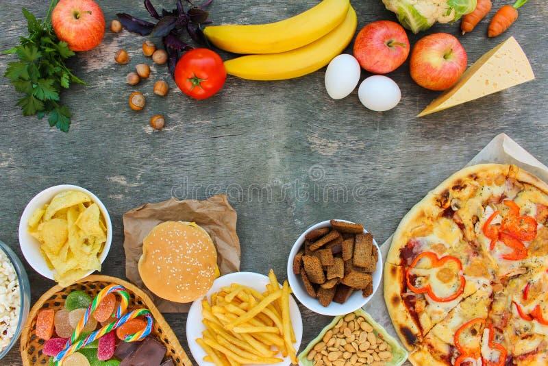 Fastfood und gesundes Lebensmittel auf altem hölzernem Hintergrund stockfoto