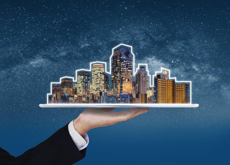 Fastighetaff?r, byggnadsteknologi och smart stad Affärsmanhand som rymmer den digitala minnestavlan med byggnadshologrammet arkivfoto