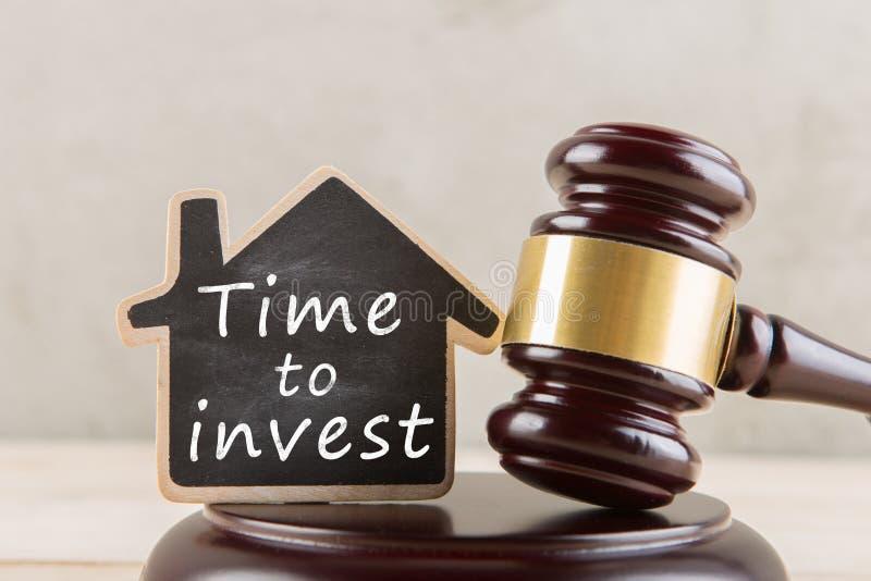 Fastighetbegrepp - auktionauktionsklubba och litet hus med inskriften Tid som ska investeras royaltyfria bilder