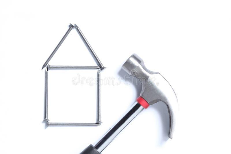Fastighetbegrepp: form av ett hus som göras med, spikar och en hammare som isoleras på vit bakgrund med kopieringsutrymme för din royaltyfri bild