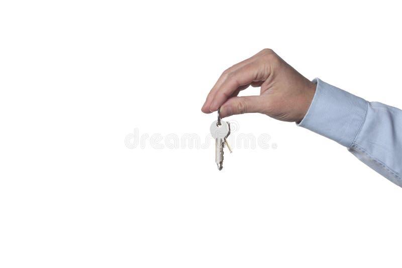 Fastighetbegrepp: mans hand som rymmer tangenter som isoleras på vit bakgrund med urklippbanan inklusive och kopieringsutrymme fö arkivbilder