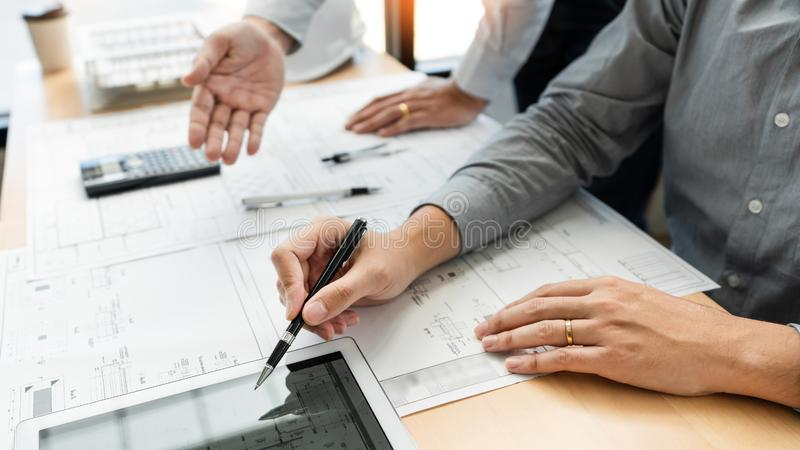 Fastighetbegrepp, två tekniker och arkitekt som diskuterar den funktionsdugliga och digitala minnestavlan för ritningdata på kons royaltyfri foto