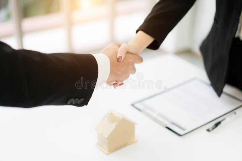 Fastighetmäklare och kund som skakar händer, når underteckning av ett avtal: fastighet-, bostadslån- och försäkringbegrepp arkivfoton