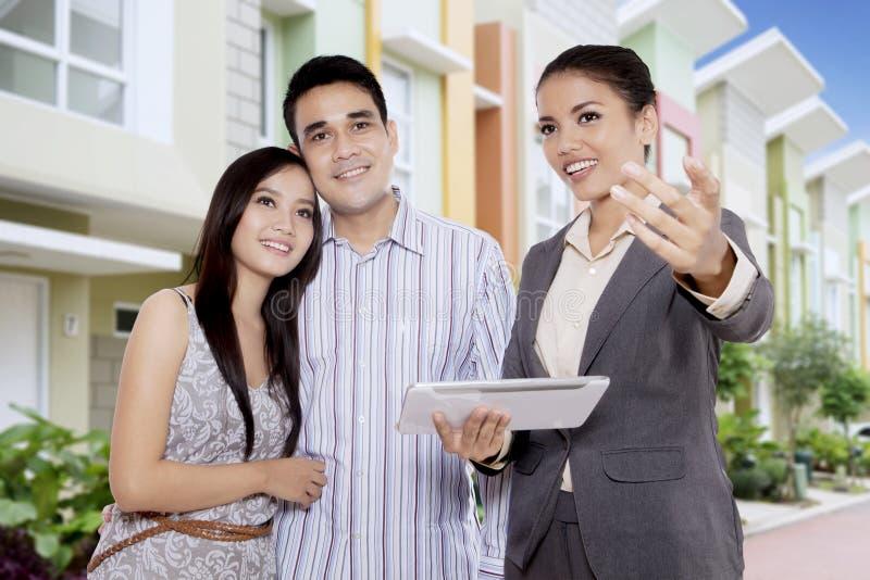 Fastighetmäklare som visar ett nytt hus för försäljning till ett ungt asiatiskt par royaltyfria foton