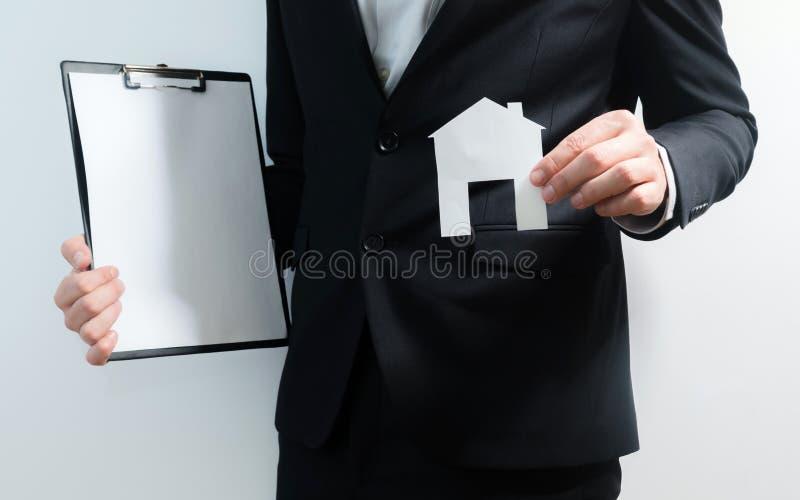 Fastighetsmäklare, fastighetsmäklareinnehavminnestavla och pappersmodell av ett hus Få tillträde för att returnera Investering- o arkivfoto