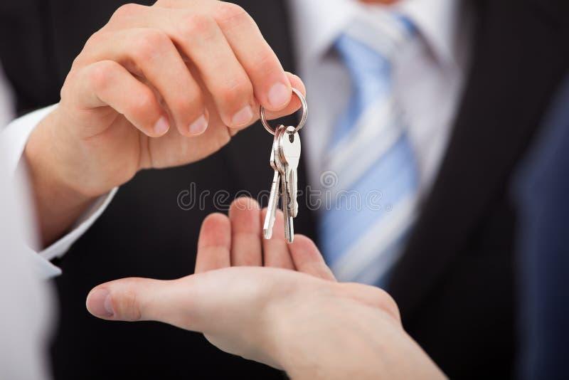 Fastighetsmäklare som ger hustangenter till mannen arkivfoton