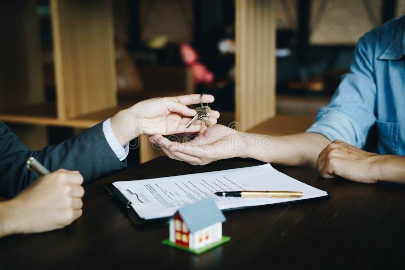 Fastighetsmäklare som ger tangenter till nya egendomsägare, når underteckning av avtalet, av begreppsöverenskommelse och av fasti fotografering för bildbyråer