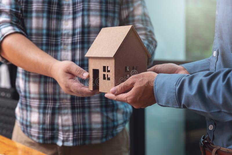 Fastighetsmäklare som räcker över en husmodell med hans klient, når att ha förseglat avtal royaltyfri bild