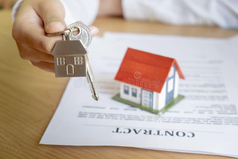 Fastighetsmäklare som räcker över hustangenter arkivfoto