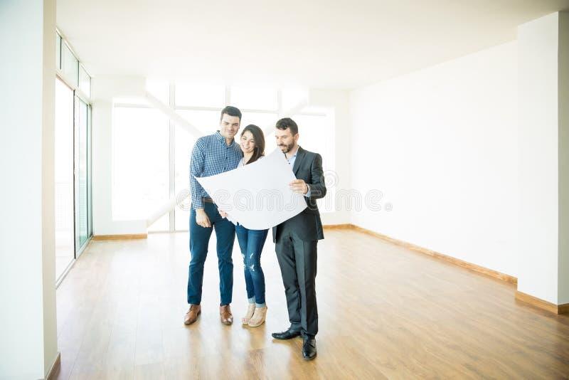 Fastighetsmäklare som visar arkitektoniskt plan till par i nytt hus arkivbild