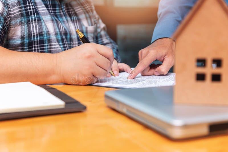 Fastighetsmäklare som visar hans klient var han måste underteckna ett avtal på att försegla avtal royaltyfria bilder