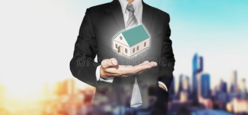 Fastighetsmäklareaffärsman med den hem- modellen förestående, med stads- stadssikt i soluppgångbakgrund arkivfoto