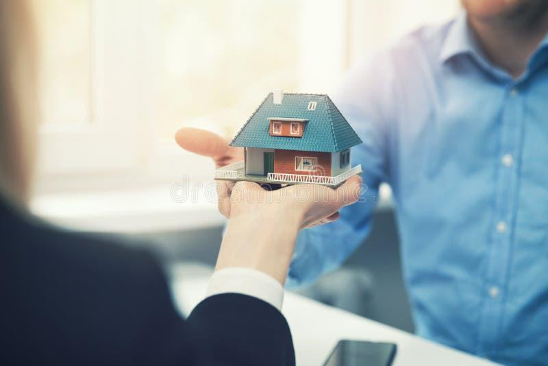 Fastighetsmäklarearkitekt som framlägger husmodellen till kunden arkivbild