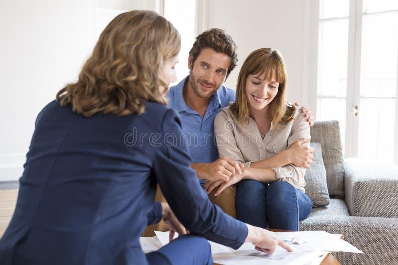 Fastighetsmäklaremedel som framlägger ett avtal för lägenhetinvestering till ett gladlynt par royaltyfri bild