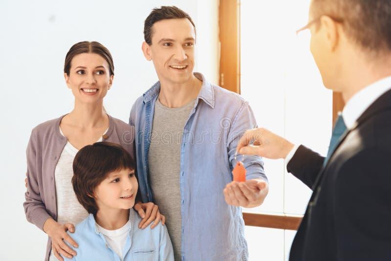 Fastighetsmäklaren framlägger tangenter till familjen i ny lägenhet med kartonger arkivfoto