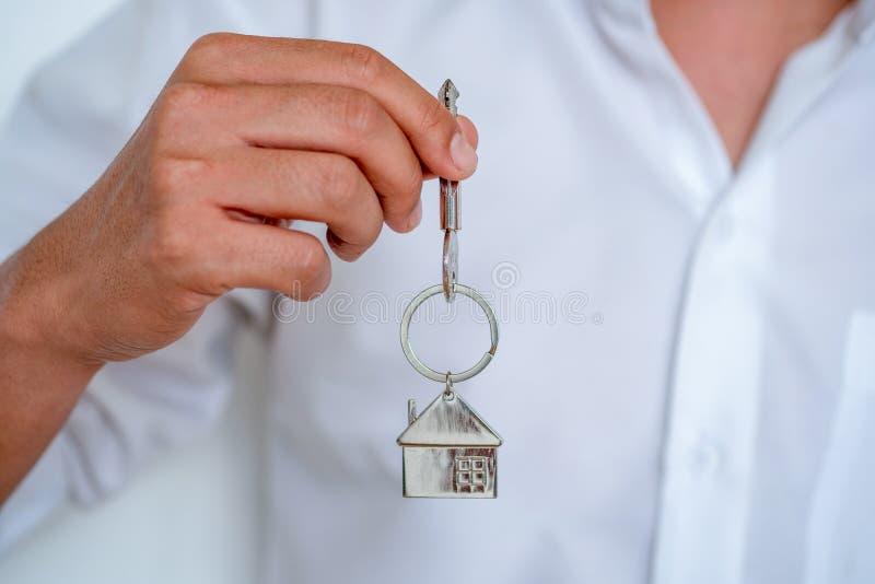 Fastighetsmäklaren som räcker över hustangenter, manhanden som rymmer tangent med huset, formade keychain, stänger sig upp fokus arkivfoton