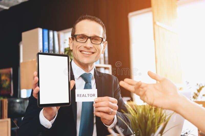 Fastighetsmäklaresammanträde på skrivbordet i regeringsställning Fastighetsmäklaren är den hållande minnestavlan, fader pekar på  royaltyfria foton