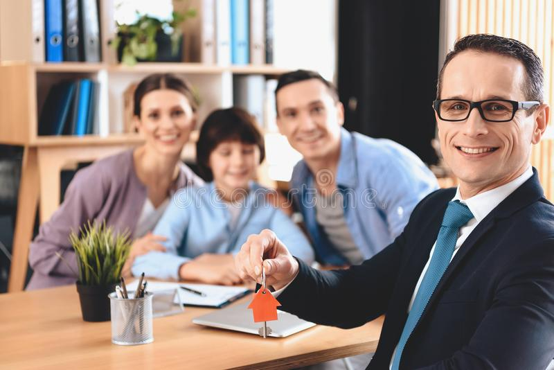 Fastighetsmäklaresammanträde på skrivbordet i regeringsställning Fastighetsmäklaren framlägger tangenter för ny lägenhet med fami arkivfoton