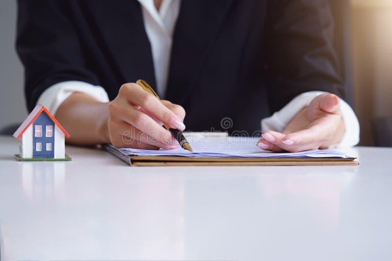 Fastighetsm?klarebruk pennan som pekar p? dokumentvisning var att underteckna Underteckning av ett pappers- dokument f?r k?pande  arkivbild