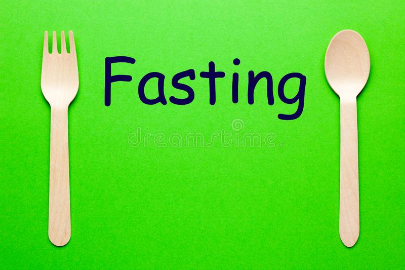 Fasting Eat Concept. Fasting word with spoon and fork on green background. Eat concept stock image